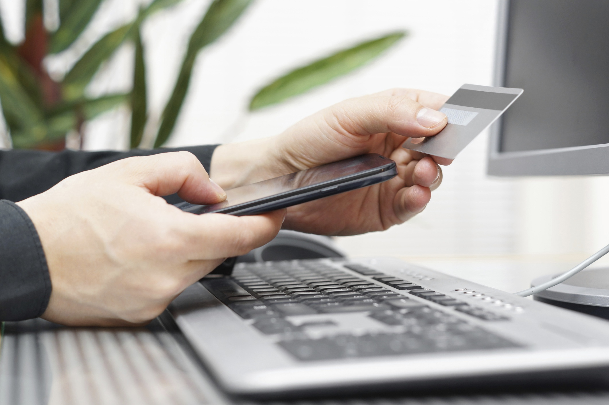 Man_using_a_credit_card_and_mobile_phone_for_payment_2123x1415.jpg